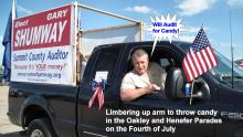 Gary limbering up arm to throw candy in Oakley and Henefer Parades on the 4th of July